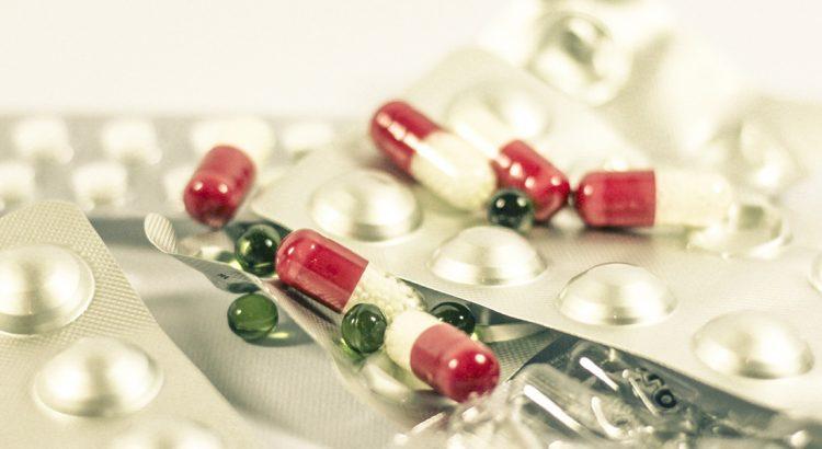 Różnokolorowe tabletki rozsypane na białym stole.