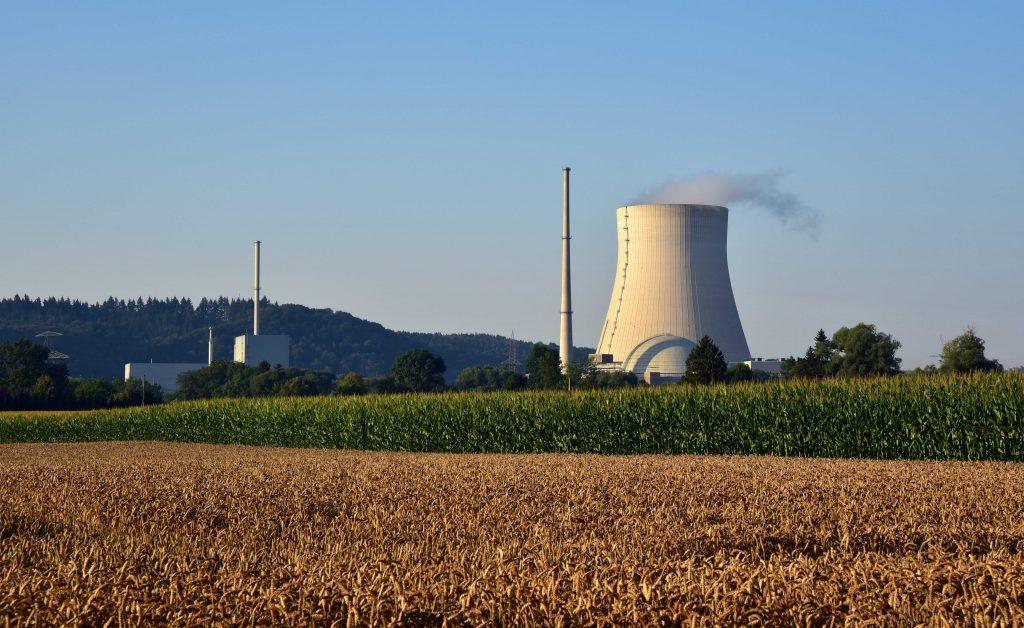 Kominy elektrowni atomowej pośród pól.