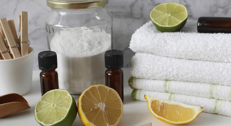 Na białym stoliku leżą białe ręczniki, obok nich stoi słoik z proszkiem do prania, przekrojone na pół cytryny, olejki eteryczne w buteleczkach oraz kubek z klipsami do wieszania prania. Nagłówek do artykułu Enzymy.