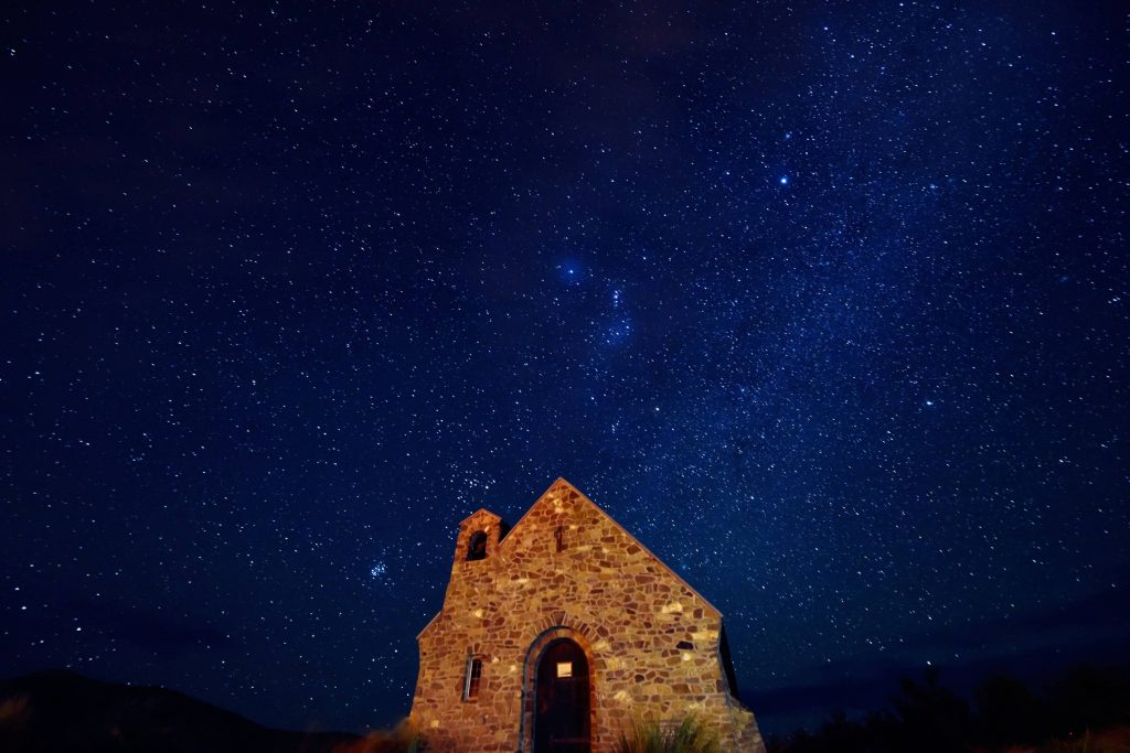 Rozgwieżdżone niebo, na dole na środku kamienny, podświetlony dom.