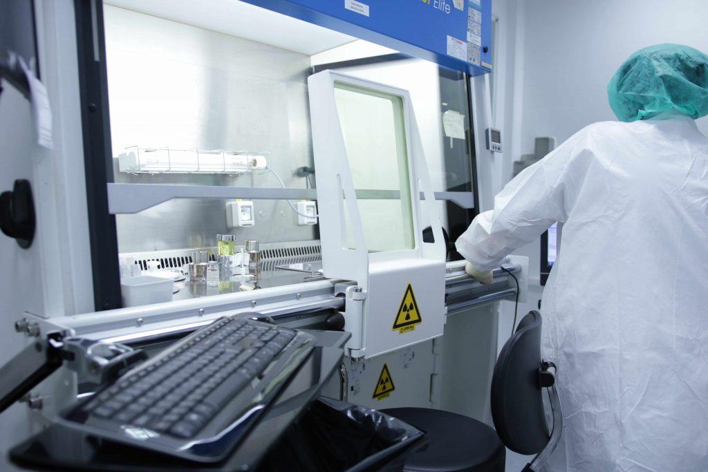 Laboratorium z oznaczeniami radioaktywności. Po prawej stronie osoba w fartuchu i czepku, odwrócona tyłem.