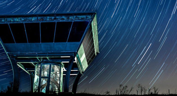 Rozgwieżdżone niebo uchwycone w dlugiej ekspozycji, na pierwszym planie stalowo-szklany budynek.