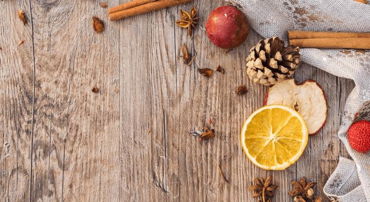 Nagłówek eksperymenty świąteczne z dziećmi. Na drewnianym stole leżą suszone pomarańcze, szyszki i jabłka w klimatach świątecznych.