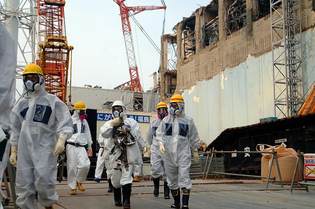 Grupa mężczyzn w białych kombinezonach, z kaskami na głowie i specjalnymi maskami na twarzy. W tle elektrownia w Fukushimie.