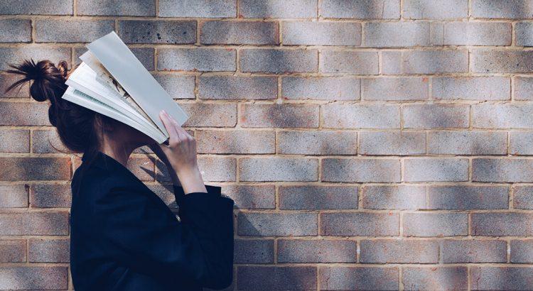 Dziewczyna trzymająca otwartą książkę na twarzy stoi na tle ceglanej ściany.
