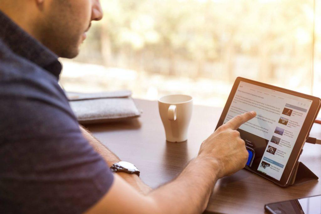 Mężczyzna siedzący przy biurku pokazuje palcem na artykuł wyświetlony na tablecie.