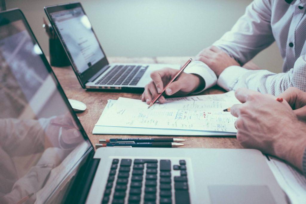 Dwa laptopy leżące na biurku, pomiędzy nimi kartki papieru i widoczne ręce do ramion należące do ludzi, którzy pokazują coś ołówkiem na dokumentach.