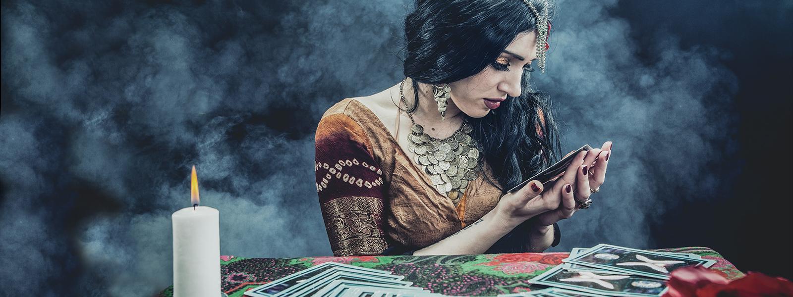 Kobieta - wróżka, ubrana w suknię i dużą ilość biżuterii siedzi nad stołem, na którym rozłożone są karty.