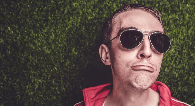 Afantazja. Mężczyzna w bluzie z kapturem i okularami przeciwsłonecznymi w charakterystyczny sposób wydyma usta.