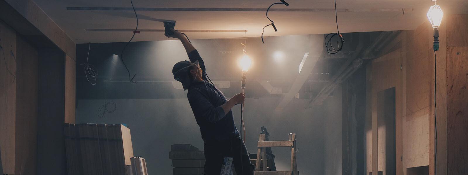 Robotnik malujący sufit na budowie.