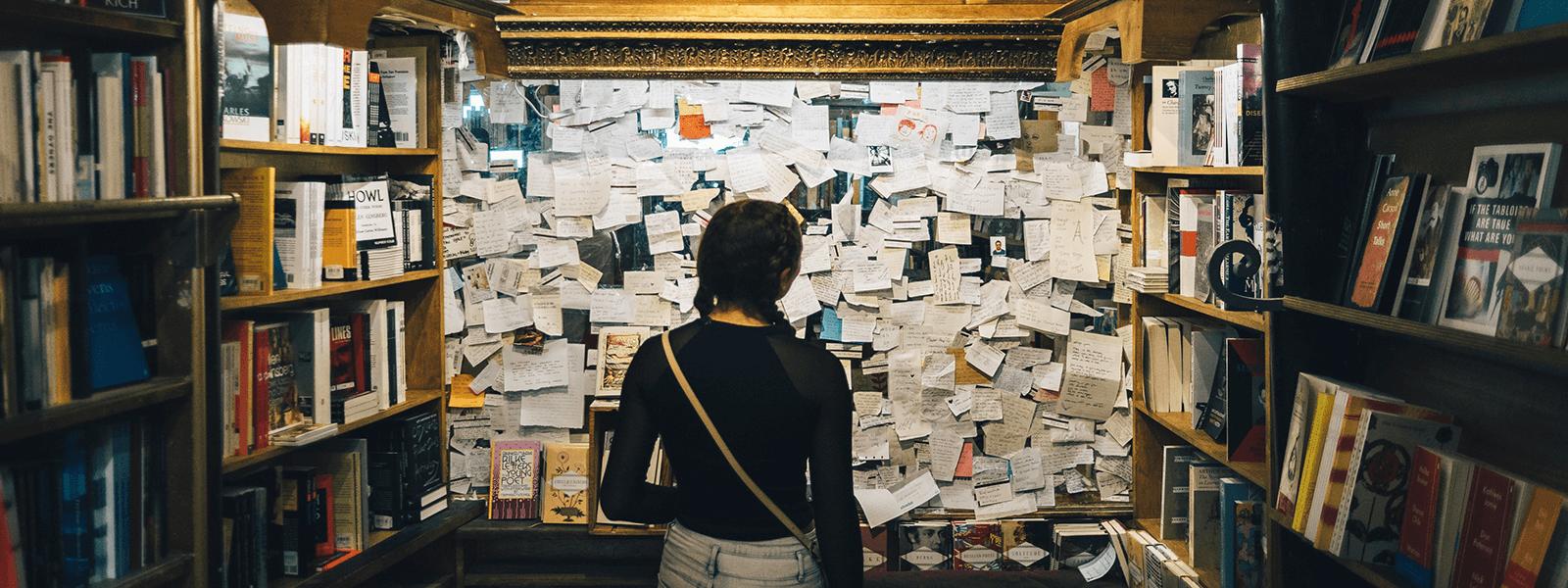 Dziewczyna w księgarni stoi przed tablicą z mnóstwem zapisanych karteczek.