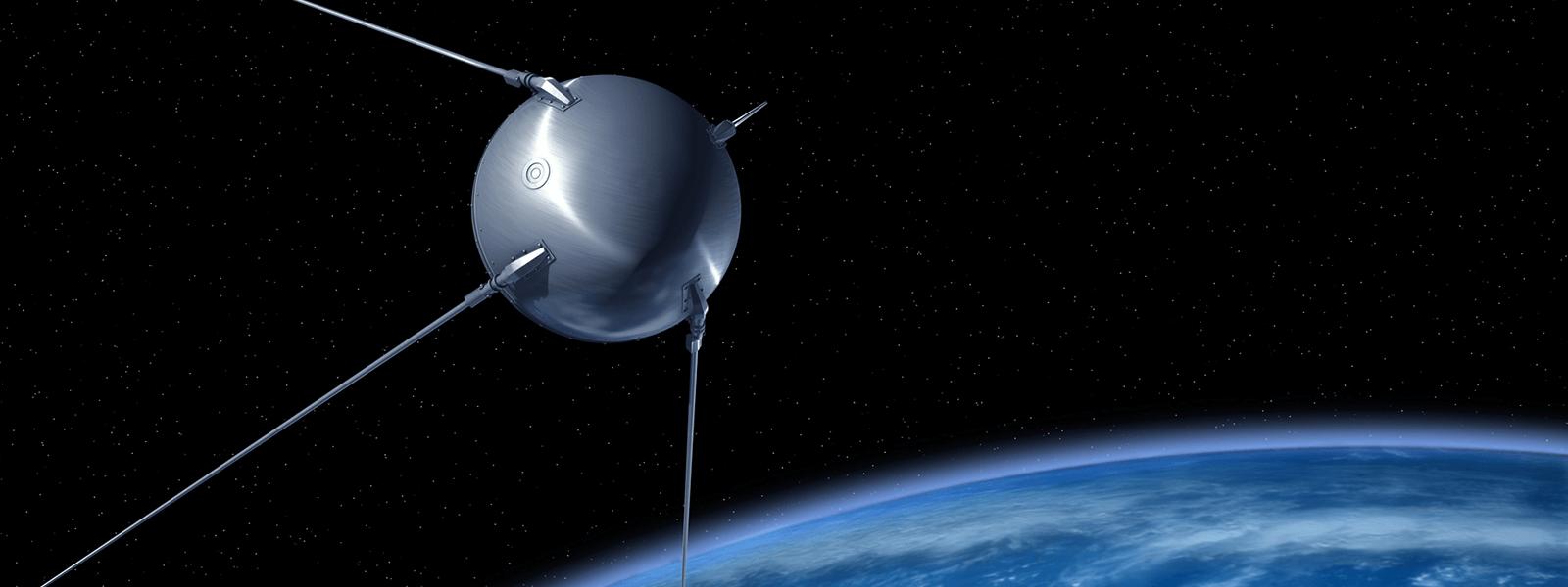 Sputnik na tle rozgwieżdżonego nieba. Na dole Ziemia.