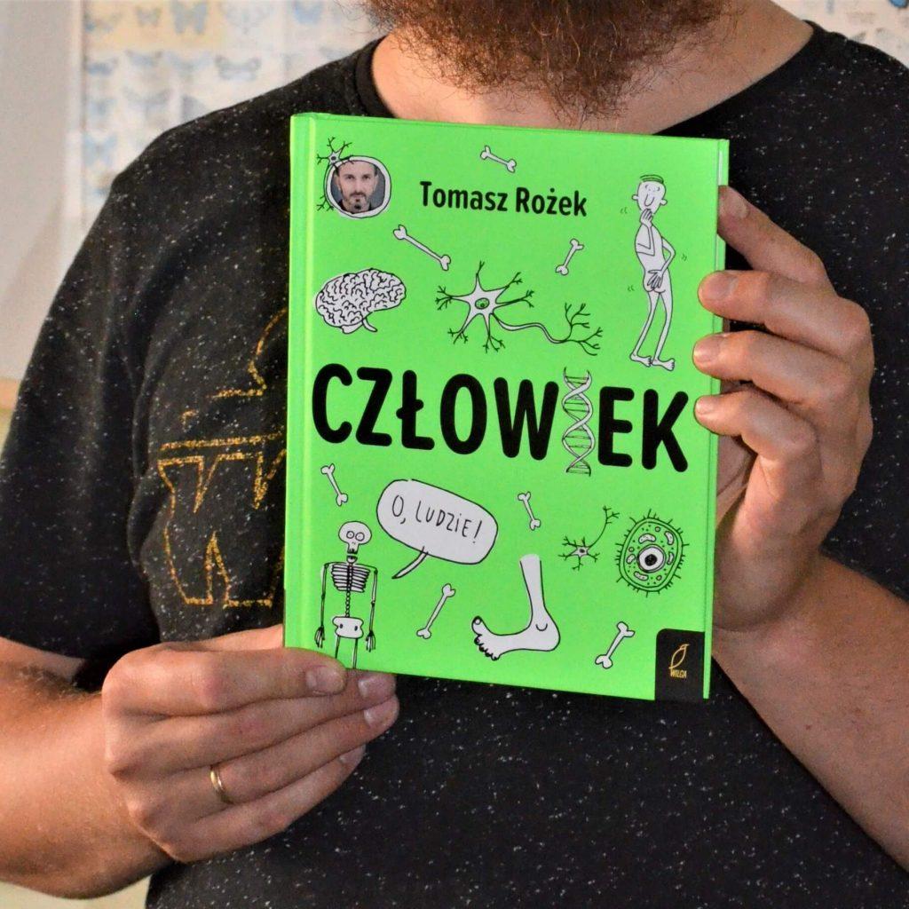 """Książka Tomasza Rożka """"Człowiek"""" trzymana w rękach"""