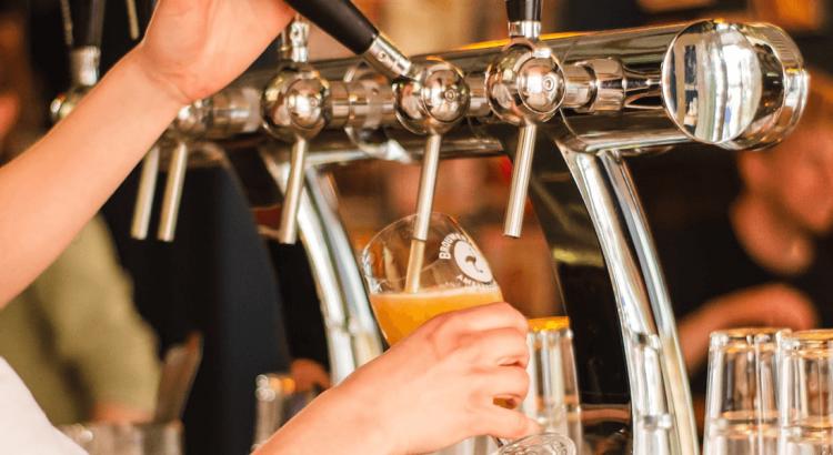 Ręka nalewająca piwo z dozownika w pubie - jednostki miary